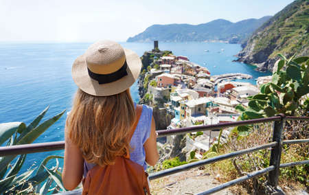 Summer holiday in Italy. Back view of young woman with hat and backpack looking at Vernazza town in the Cinque Terre, Italy.