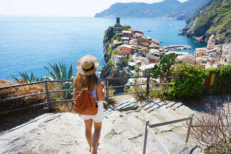 Tourism in Italy. Young female backpacker going downstairs in the Cinque Terre National Park. Beautiful girl walks the Azure Trail and looking at Vernazza town, Italy.