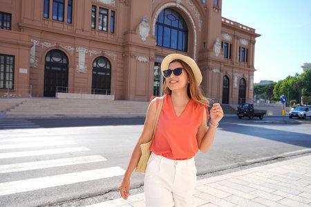 Visiting Bari. Portrait of happy smiling young fashion woman walking in Bari, Italy.
