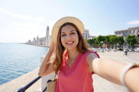 Smiling stylish woman takes self portrait on seaside town of Bari, Apulia, Italy Archivio Fotografico