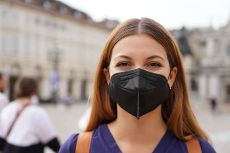 Portrait of student girl wearing a protective KN95 FFP2 black mask looking at camera with urban background Archivio Fotografico