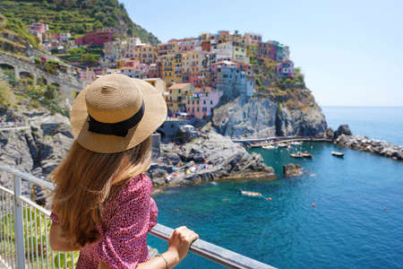 Holidays in Italy. Young traveler woman with hat and dress looking the amazing panoramic of Manarola village in Cinque Terre, Italy.
