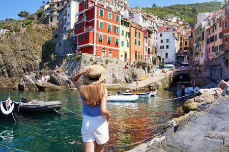 Holidays in Italy. Beautiful woman walking in Riomaggiore harbor looking at quaint village overhanging cliffs, Cinque Terre, Italy. Archivio Fotografico