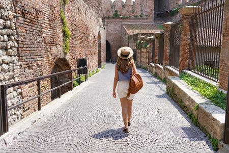 Beautiful tourist woman walking in the medieval city of Verona on Castelvecchio bridge, Italy Archivio Fotografico