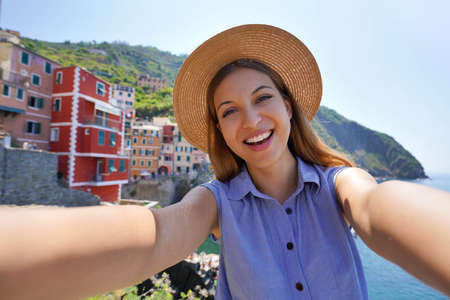 Smiling tourist girl taking selfie photo on sunny day in Riomaggiore village, Cinque Terre, Italy