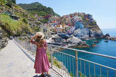 Young traveler woman with hat and dress descend along the promenade of Manarola looking at fantastic panoramic view of Manarola village in the Cinque Terre, Italy Archivio Fotografico