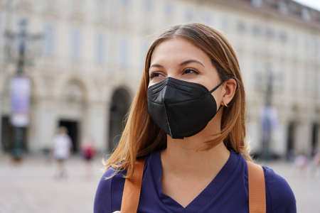 Portrait of student girl wearing a protective KN95 FFP2 black mask walking in city street