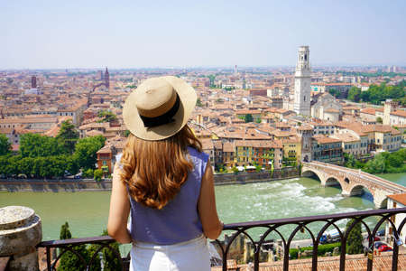 Woman sightseeing Verona city landmarks vacations in Italy travel lifestyle girl tourist relaxing at viewpoint Old Town aerial view architecture