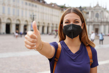 Optimistic traveler woman wearing black protective mask KN95 FFP2 showing thumbs up in city square