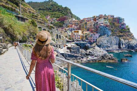 Romantic trail in Italy. Rear view of pretty girl walking on the promenade towards Manarola village, Italy. Archivio Fotografico