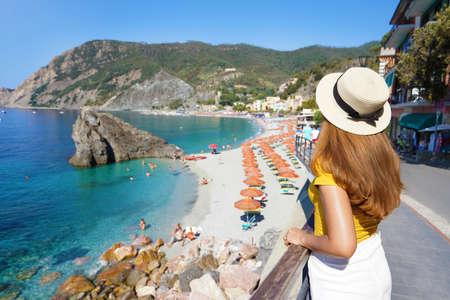 Summer holiday in Italy. Back view of young woman with hat in Monterosso al Mare village, Cinque Terre, Italy. Archivio Fotografico