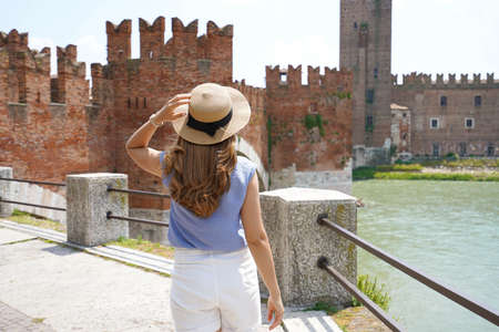 Promenade riverside in Verona, Italy. Back view of lady walking along promenade with medieval Castelvecchio and on the background.
