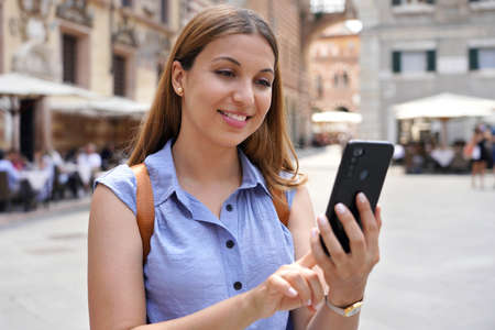 Close up portrait of a young stylish woman holding a smartphone