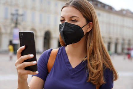 Close up of girl with black protective mask FFP2 KN95 using smart phone with urban background