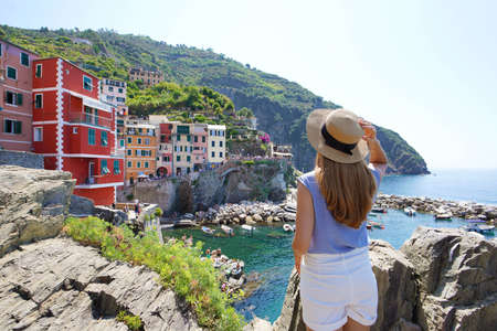 Holidays on Cinque Terre, Italy. Tourist girl looking at village nestled between the rocks overhanging cliffs, Riomaggiore, Italy.