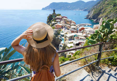 Summer tourism in Italy. Rear view of traveler girl with hat and backpack looking at Vernazza village in Liguria, Italy.