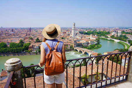 Romantic traveler girl visiting Verona city of love. Back view of young female backpacker enjoying cityscape of Verona, Italy.