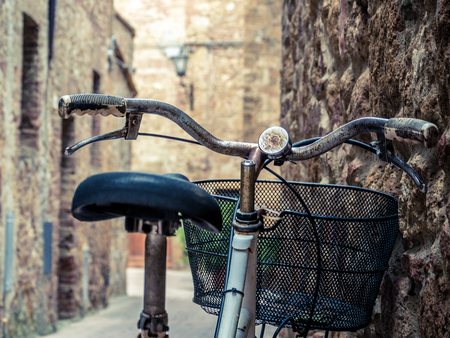 Red old bicycle in a little alley of a medieval village