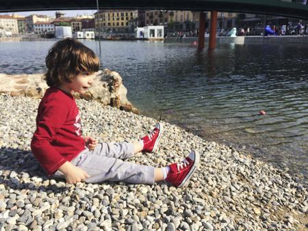 Child throwing stones at Darsena in Milan in spring