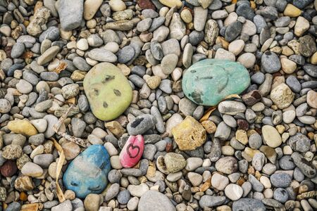 Stones painted by children on a beach