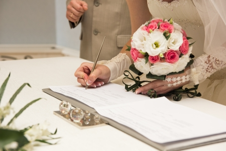 Brides hand closeup signing a wedding contract photo