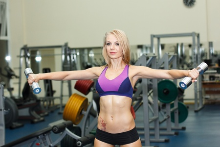 Fitness girl making exercise with dumbbells photo