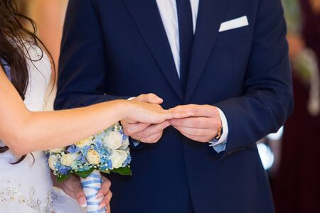 Happy bride and groom hands changing rings during wedding ceremony photo