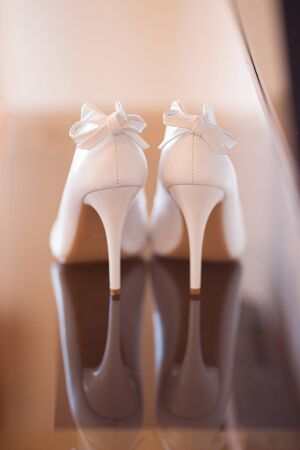 foot ware: Elegant pair of white bridal shoes on the floor