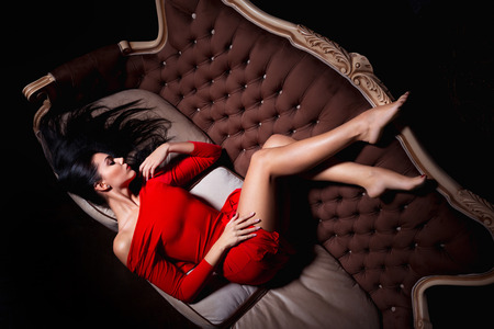 Attractive woman in red dress posing on luxury sofa