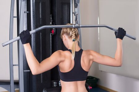 athletic: Athletic woman performing back exercise in gym
