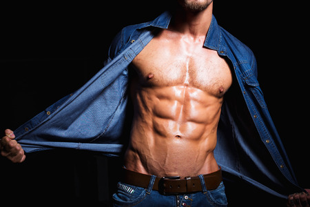 naked abs: Muscular and sexy body of young man in jeans shirt with perfect abs