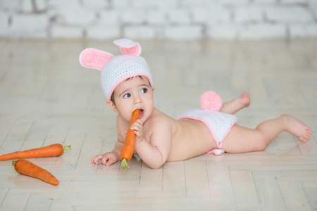 Portrait of a cute baby dressed in bunny ears eating a carrot photo