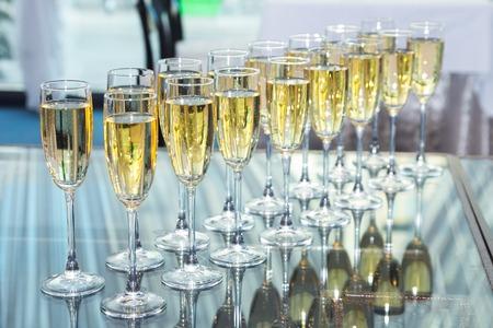brindisi spumante: Bicchieri eleganti con champagne in piedi in fila sul tavolo che serve durante la festa o celebrazione Archivio Fotografico