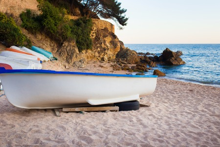 dinghies: Old small boats on sandy beach. Weathered and dirty dinghies scattered across the sand. Stock Photo