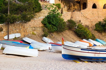dinghies: Many old small boats on sandy beach. Weathered and dirty dinghies scattered across the sand.
