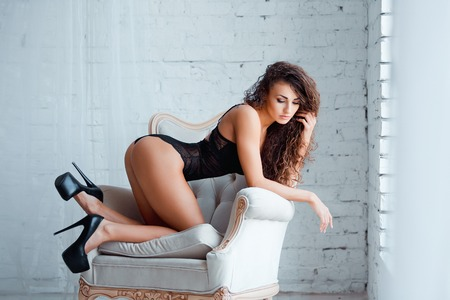 nude female buttocks: Perfect, sexy body, legs and ass of young woman on high heels wearing seductive black lingerie. Beautiful hot female in lacy bodysuit posing on luxury vintage chair