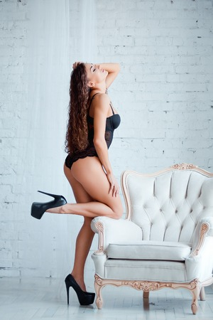 nude ass: Perfect, sexy body, legs and ass of young woman wearing seductive black lingerie. Beautiful female in bodysuit on luxury vintage chair. Stock Photo