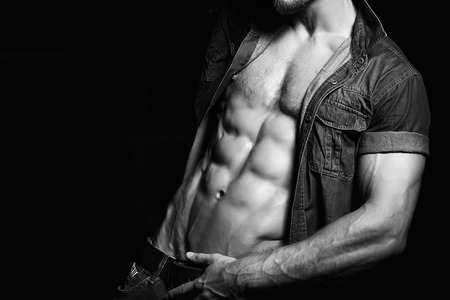 six pack: Muscular and sexy young man in jeans shirt with perfect fitness body. Black and white Stock Photo