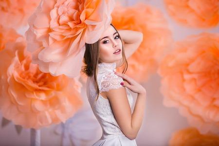 Het jonge mooie meisje stellen in papieren bloemen in de lente studio