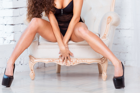 hot girl nude: Perfect, sexy legs and ass of young woman wearing seductive black lingerie, sitting on luxury vintage chair.