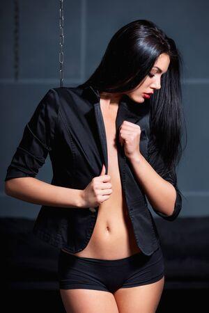 seni: Bella giovane donna sexy posa indossando giacca nera sul corpo nudo.