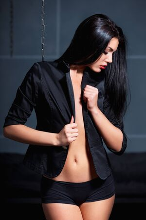 mujeres desnudas: Hermosa mujer joven atractiva que presenta el uso de chaqueta negro sobre el cuerpo desnudo. Foto de archivo