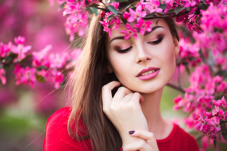 attractive female: Happy beautiful young woman in spring blossom park. Attractive female in red dress enjoy spring fresh pink flowers. Stock Photo