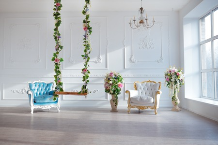 sitting on sofa: White leather vintage style chair in classical interior room with big window and spring flowers.