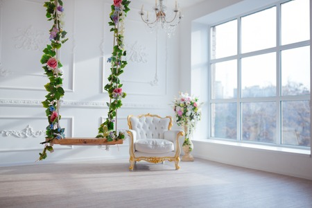 White leather vintage style chair in classical interior room with big window and spring flowers.