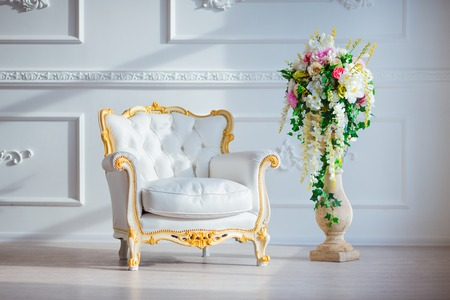 antique wood: White leather vintage style chair in classical interior room with big window and spring flowers.