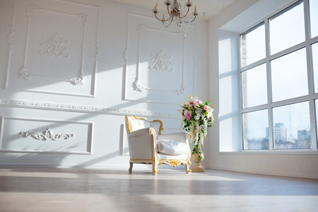 antique chair: White leather vintage style chair in classical interior room with big window and spring flowers.