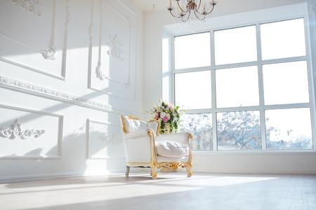 cuero blanco silla de estilo Vintage en sala interior clásico con flores grandes ventanas y primavera.