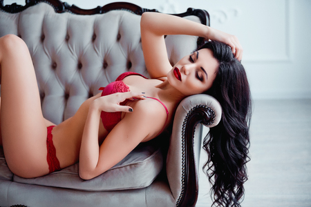 nude female buttocks: Perfect, sexy body, legs and ass of young woman wearing seductive red lingerie. Beautiful hot female in underware posing on luxury vintage sofa.