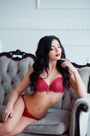 nude female body model: Perfect, sexy body, legs and ass of young woman wearing seductive red lingerie. Beautiful hot female in underware posing on luxury vintage sofa.